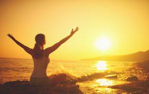 yoga at sunset on beach woman doing yoga